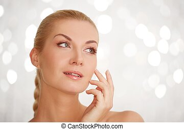 Beautiful woman touching her face.