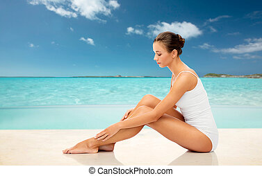 beautiful woman touching her smooth legs on beach - beauty,...
