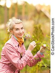 Beautiful woman touching young plant in the garden