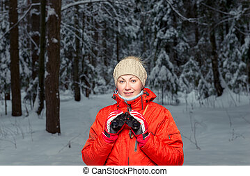 beautiful woman tourist with binoculars in a winter forest