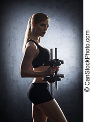 Beautiful woman trainig with dumbbells