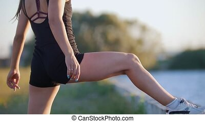 Beautiful Woman Trains Her Legs Before Running On The...
