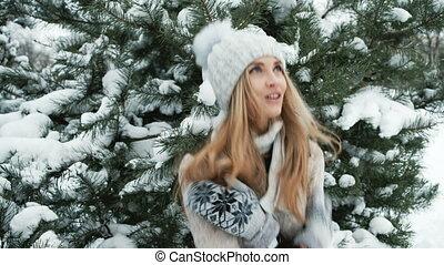 Beautiful woman tries to get warm, winter landscape.