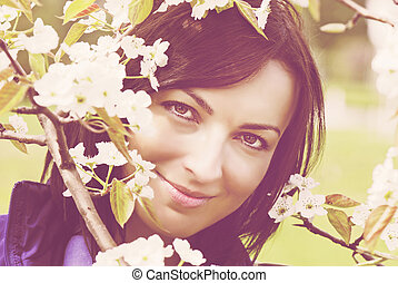 Beautiful woman under blooming tree