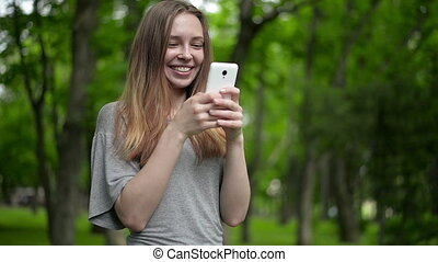 Beautiful woman uses cell smartphone outdoors in the park  - detail