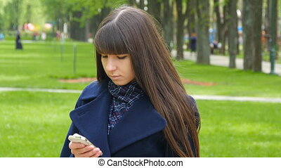 Beautiful woman uses cell smartphone outdoors in the park  - detail . Young attractive happy girl relaxes in a city park