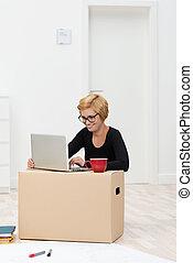 Beautiful woman using a carton as a desk