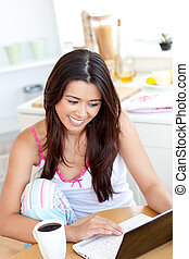 Beautiful Woman using a laptop in the kitchen
