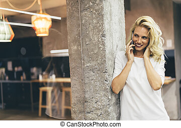 Beautiful woman using cell phone in kitchen
