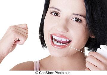Beautiful woman using dental floss