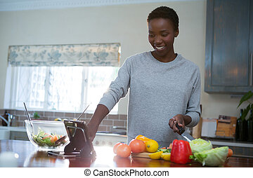 Beautiful woman using digital tablet in kitchen