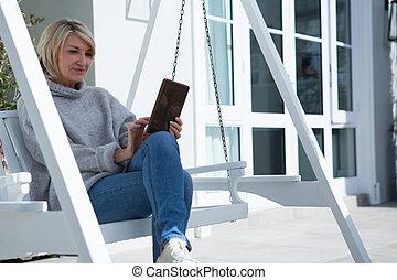 Beautiful woman using digital tablet in porch
