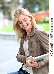 Beautiful woman using electronic tablet in public park