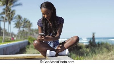 Beautiful woman using phone on fence - Beautiful young black...