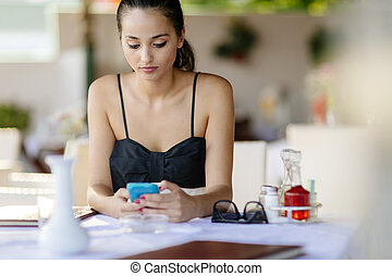 Beautiful woman using phone while waiting for meal in restaurant