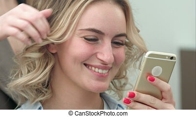 Beautiful woman using smartphone in a beauty salon, while having a hair styling