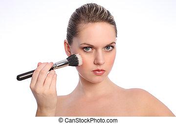 Beautiful woman using stippling make up brush