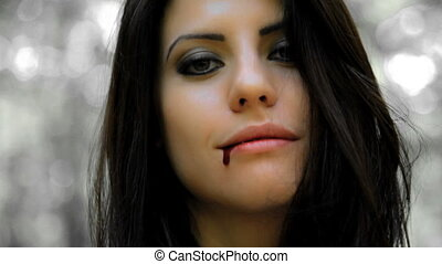 Gorgeous female vampire smiling with blood coming out of her mouth