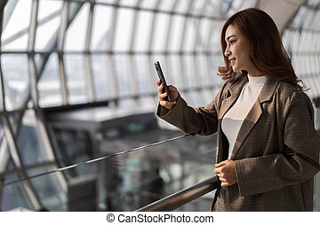 beautiful woman waiting for flight and using smart phone in airport