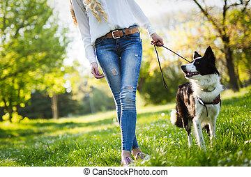 Beautiful woman walking cute dog in nature