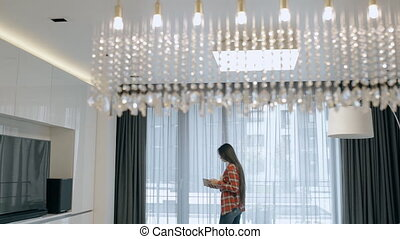 Beautiful woman walking in living room and reading book....