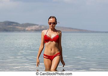 Beautiful woman walking in sea water