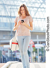 beautiful woman walking in the city street with mobile phone