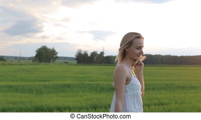 beautiful woman walking in the field with a bouquet of flowers