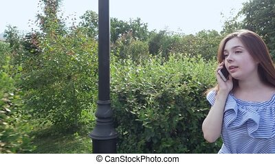 Beautiful woman walking in the park and talking on the...