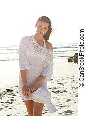 Beautiful woman walking on beach with sun dress