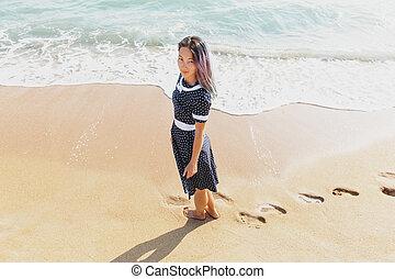Beautiful woman walking on sand beach.