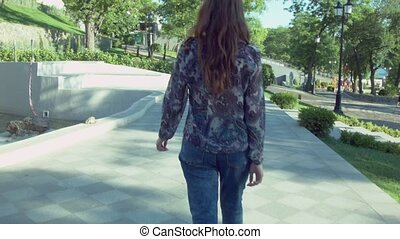 beautiful woman walking on the sidewalk around street. She is a young