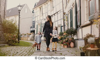 Beautiful woman walking with two children. Holding hands....