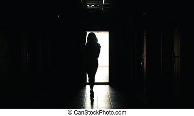 Beautiful woman walks in a dark corridor, silhouette, close...