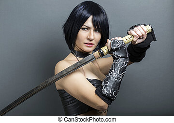 Beautiful woman-warrior with sword on grey background.