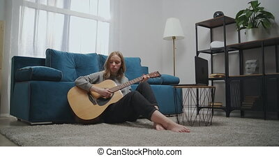 Beautiful woman watching online lesson while sitting on the floor in the room. Girl learns to play the guitar on isolation. An aspiring musician learns to play a musical instrument using a laptop. High quality 4k footage