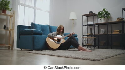 Beautiful woman watching online lesson while sitting on the floor in the room. Girl learns to play the guitar on isolation. An aspiring musician learns to play a musical instrument using a laptop. Long shot. High quality 4k footage