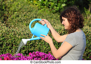 Beautiful woman watering flowers with a watering can