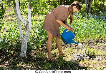 Beautiful woman watering the garden