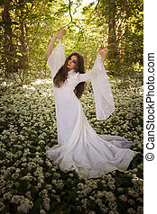 Beautiful woman wearing a long white dress dancing in a forest