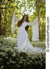 Beautiful woman wearing a long white dress dancing in a forest
