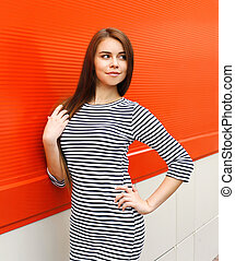 Beautiful woman wearing a striped dress in city over red background