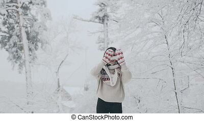 Beautiful woman wearing a warm winter sweater and scarf, hiding her eyes with hands in mittens, enjoying a snowy winter day in nature