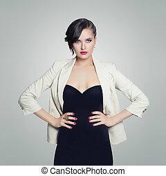Beautiful woman wearing black dress posing on white background
