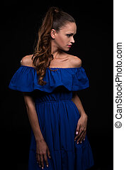 beautiful woman wearing blue dress on black background