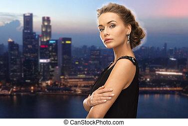 beautiful woman wearing earrings over night city