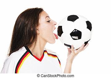 beautiful woman wearing football shirt licking on a football on white background