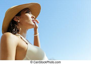 Beautiful woman wearing hat in summer