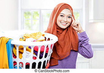 beautiful woman wearing hijab carrying laundry basket with hand in her heads pretend to thinking