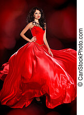 Beautiful woman wearing in magnificent red dress isolated on black background. Studio photo. Fashion.